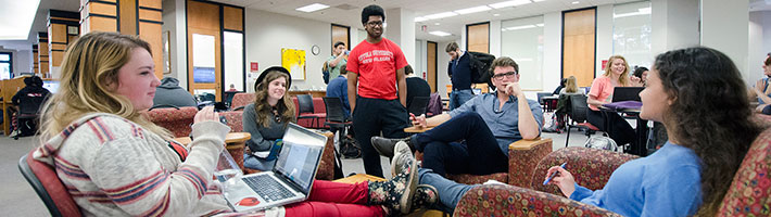 Photo of students sitting on chairs gathered in a circle in Monroe Library