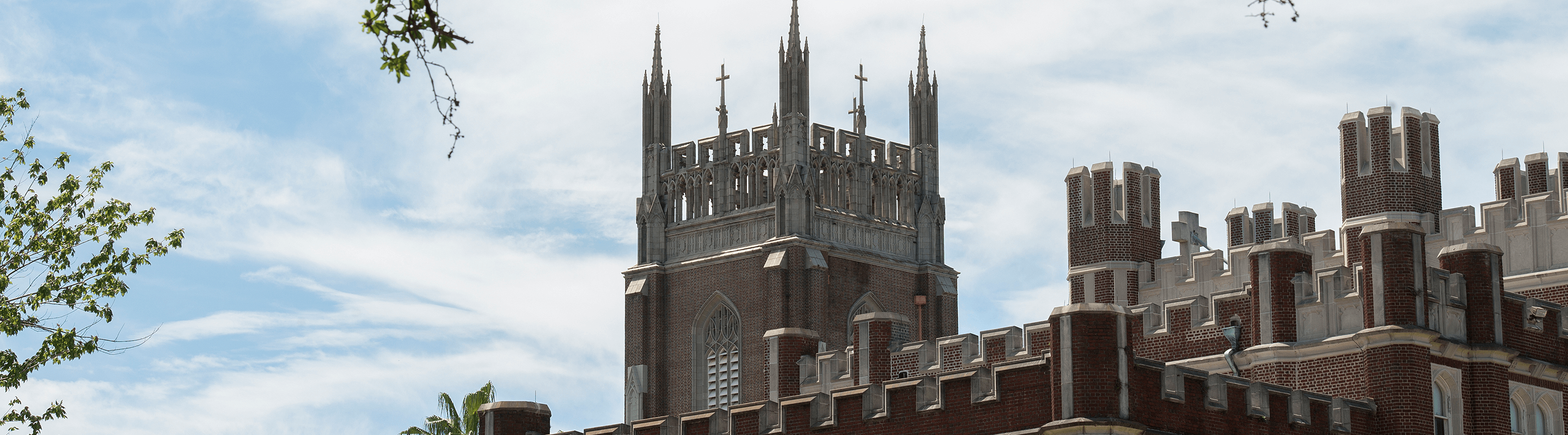 Image of tower of Marquette Hall against blue sky, 3/4 view
