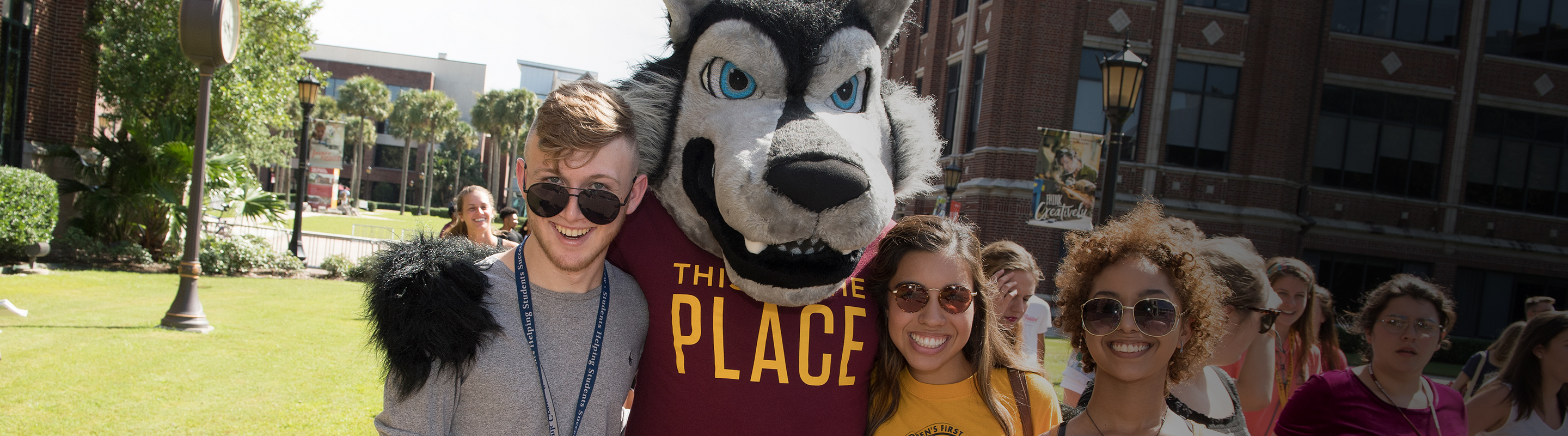 Group of smiling students with wolf mascot Havoc